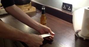 Aprire una bottiglia di birra con un foglio di carta